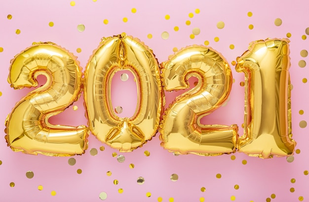 2021 balões de ar dourados de feliz ano novo com confetes na superfície rosa