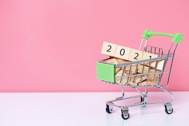 2021 com cubo de madeira no carrinho de compras em fundo rosa. conceito de feliz ano novo.