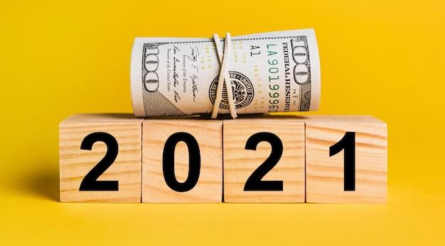 2021 com dinheiro em um fundo amarelo.