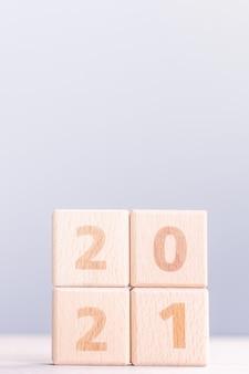 2021 conceito de design abstrato de ano novo - cubos de bloco de madeira numéricos isolados na mesa de madeira e fundo azul claro névoa