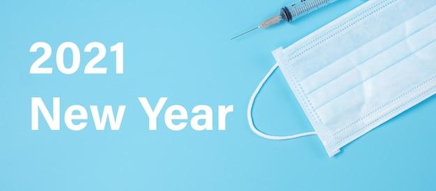 2021 feliz ano novo com a dose do frasco da vacina e a seringa com agulha para drogas injetáveis no laboratório do hospital.