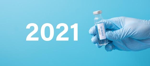 2021 feliz ano novo com o frasco da vacina covid-19 contra a infecção por coronavírus nas mãos do médico