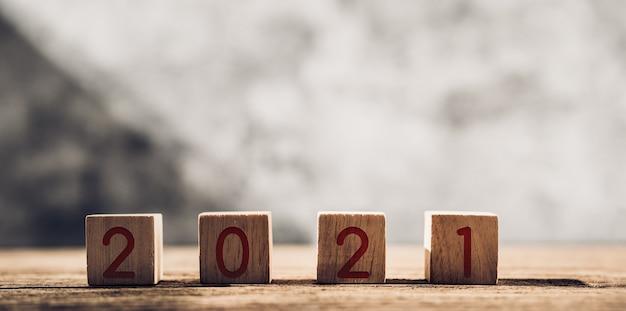 2021 feliz ano novo em bloco de madeira na mesa de madeira e parede de concreto com luz do sol da janela