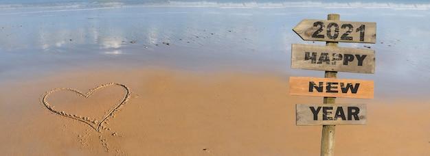 2021 feliz ano novo escrevendo em uma placa de madeira na praia com o coração desenhando na areia