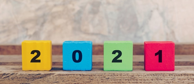 2021 feliz ano novo no bloco de madeira na mesa de madeira e muro de concreto. ano novo conceito