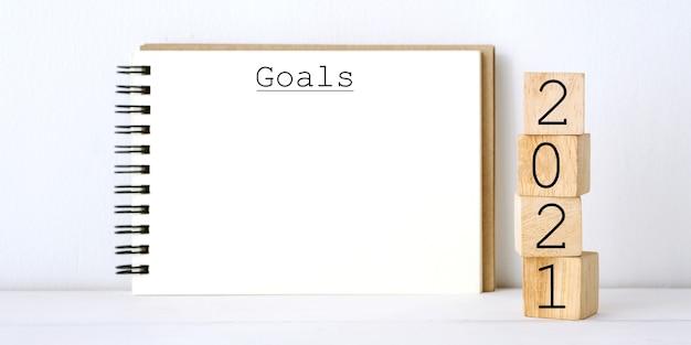 2021 gols e caderno em branco sobre fundo de mármore branco