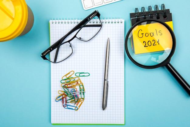 2021 objetivos em seu caderno. conceito de resoluções de ano novo. vista do topo. isolado em fundo azul