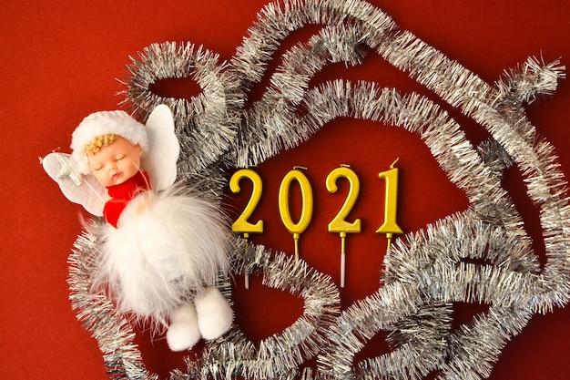 2021 projeto de ano novo. data definida por velas perto de abeto no espaço de cópia de vista superior de fundo vermelho. feliz natal, decorações de natal vermelhas. bolas de natal