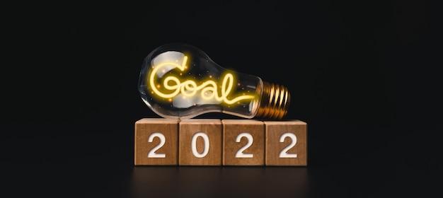 2022 banner de feliz ano novo com meta de objetivo e conceito de sucesso. os números de 2022 em blocos de cubos de madeira e uma lâmpada com palavras de luz de néon brilhantes em fundo escuro, estilo moderno e minimalista.