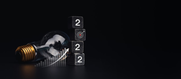 2022 banner de feliz ano novo com o conceito de objetivo e sucesso de objetivo. os 2022 números na pilha de dados pretos, gráfico de crescimento do negócio, lâmpada em fundo escuro com espaço de cópia, estilo moderno e minimalista.
