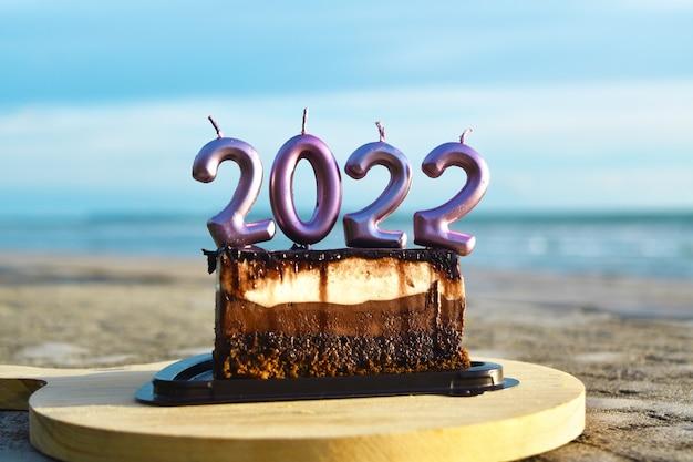 2022 feliz ano novo com bolo e velas na praia