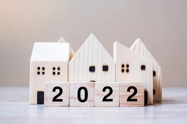 2022 feliz ano novo com modelo de casa no fundo de madeira da mesa. conceitos de banco, imobiliário, investimento, financeiro, poupança e resolução de ano novo