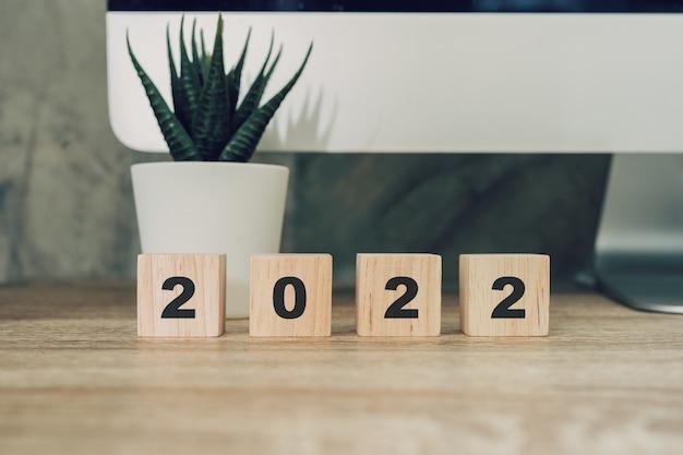 2022 feliz ano novo no bloco de madeira na mesa de madeira com a luz solar. conceito de ano novo.
