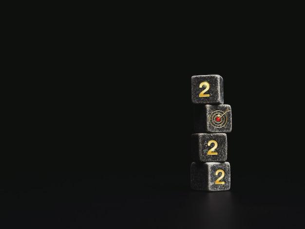 2022 feliz ano novo. o conceito de objetivo de negócios com os números dourados do ano 2022 e o símbolo do ícone de alvo vermelho na pilha de blocos de dados pretos em fundo escuro com espaço de cópia, estilo moderno e minimalista.