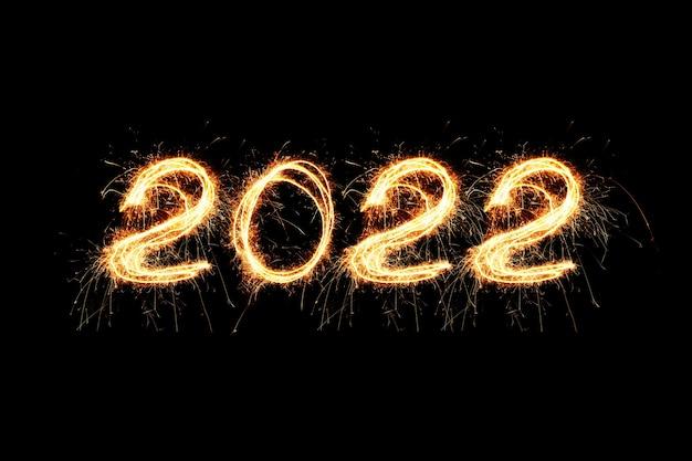 2022 fogos de artifício de feliz ano novo escritos estrelinhas cintilantes à noite. conceito de papel de parede de férias 2022