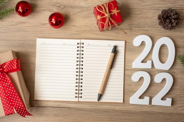 2022 reveillon com caderno, presente de natal e caneta na mesa de madeira. natal, feliz ano novo, objetivos, resolução, lista de tarefas, início, conceito de estratégia e plano