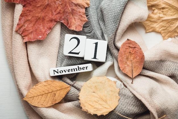 21 de novembro em calendário de cubos brancos sobre manta com folhas. postura plana