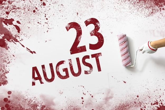 23 de agosto. dia 23 do mês, data do calendário. a mão segura um rolo com tinta vermelha e escreve uma data do calendário em um fundo branco. mês de verão, dia do conceito de ano.