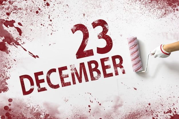 23 de dezembro. dia 23 do mês, data do calendário. a mão segura um rolo com tinta vermelha e escreve uma data do calendário em um fundo branco. mês de inverno, conceito de dia do ano.