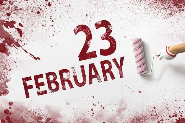 23 de fevereiro. dia 23 do mês, data do calendário. a mão segura um rolo com tinta vermelha e escreve uma data do calendário em um fundo branco. mês de inverno, conceito de dia do ano.