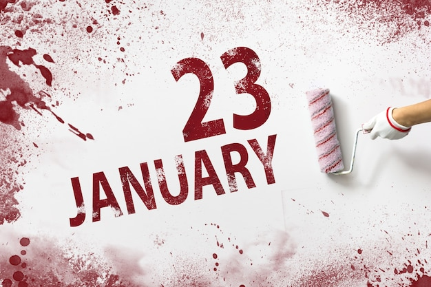 23 de janeiro. dia 23 do mês, data do calendário. a mão segura um rolo com tinta vermelha e escreve uma data do calendário em um fundo branco. mês de inverno, conceito de dia do ano.