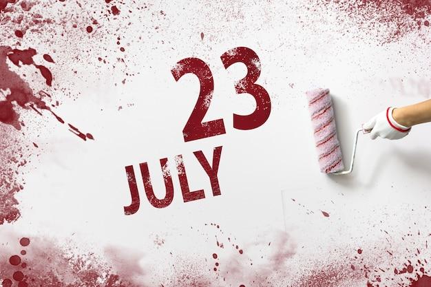 23 de julho. dia 23 do mês, data do calendário. a mão segura um rolo com tinta vermelha e escreve uma data do calendário em um fundo branco. mês de verão, dia do conceito de ano.