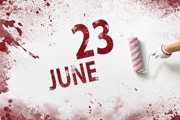 23 de junho. dia 23 do mês, data do calendário. a mão segura um rolo com tinta vermelha e escreve uma data do calendário em um fundo branco. mês de verão, dia do conceito de ano.