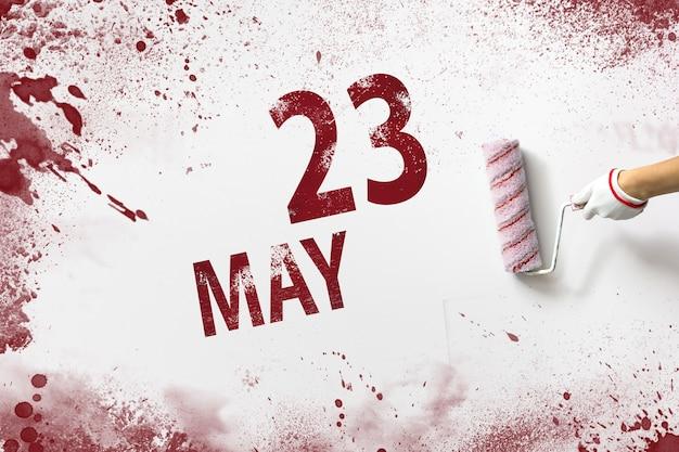 23 de maio. dia 23 do mês, data do calendário. a mão segura um rolo com tinta vermelha e escreve uma data do calendário em um fundo branco. mês de primavera, dia do conceito de ano.