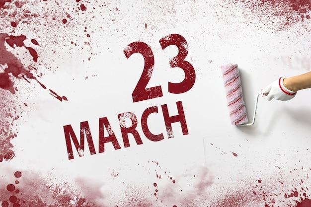 23 de março. dia 23 do mês, data do calendário. a mão segura um rolo com tinta vermelha e escreve uma data do calendário em um fundo branco. mês de primavera, dia do conceito de ano.