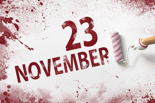 23 de novembro. dia 23 do mês, data do calendário. a mão segura um rolo com tinta vermelha e escreve uma data do calendário em um fundo branco. mês de outono, conceito de dia do ano.