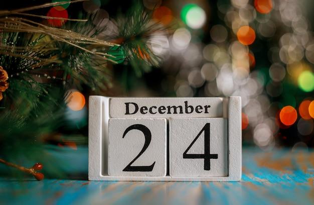 24 de dezembro no cubo de madeira com superfície de luzes da árvore de natal conceito de véspera de natal