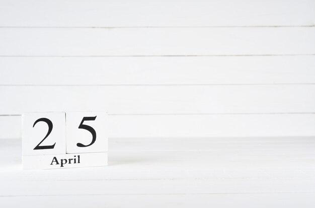25 de abril, dia 25 do mês, aniversário, aniversário, calendário de bloco de madeira sobre fundo branco de madeira com espaço de cópia para o texto.