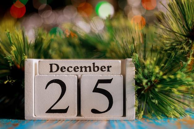 25 de dezembro no cubo de madeira com superfície de luzes da árvore de natal
