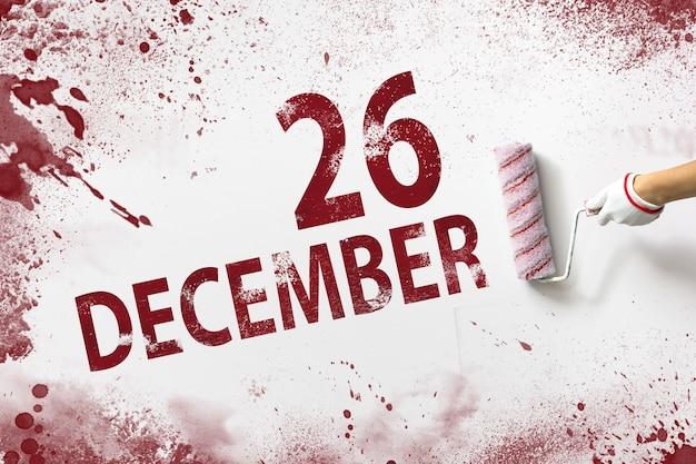 26 de dezembro. dia 26 do mês, data do calendário. a mão segura um rolo com tinta vermelha e escreve uma data do calendário em um fundo branco. mês de inverno, conceito de dia do ano.