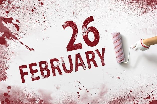26 de fevereiro. dia 26 do mês, data do calendário. a mão segura um rolo com tinta vermelha e escreve uma data do calendário em um fundo branco. mês de inverno, conceito de dia do ano.