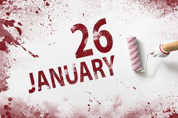 26 de janeiro. dia 26 do mês, data do calendário. a mão segura um rolo com tinta vermelha e escreve uma data do calendário em um fundo branco. mês de inverno, conceito de dia do ano.