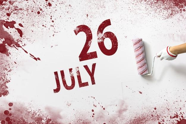 26 de julho. dia 26 do mês, data do calendário. a mão segura um rolo com tinta vermelha e escreve uma data do calendário em um fundo branco. mês de verão, dia do conceito de ano.