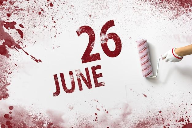 26 de junho. dia 26 do mês, data do calendário. a mão segura um rolo com tinta vermelha e escreve uma data do calendário em um fundo branco. mês de verão, dia do conceito de ano.