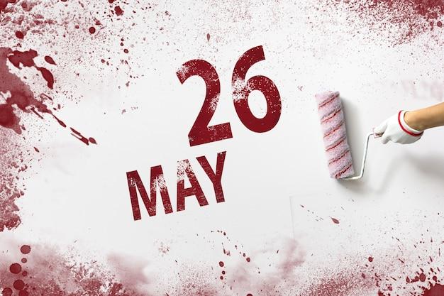 26 de maio. dia 26 do mês, data do calendário. a mão segura um rolo com tinta vermelha e escreve uma data do calendário em um fundo branco. mês de primavera, dia do conceito de ano.