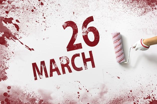 26 de março. dia 26 do mês, data do calendário. a mão segura um rolo com tinta vermelha e escreve uma data do calendário em um fundo branco. mês de primavera, dia do conceito de ano.