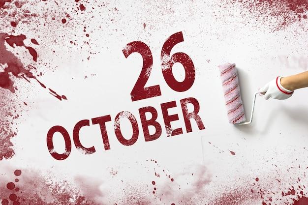 26 de outubro. dia 26 do mês, data do calendário. a mão segura um rolo com tinta vermelha e escreve uma data do calendário em um fundo branco. mês de outono, conceito de dia do ano.