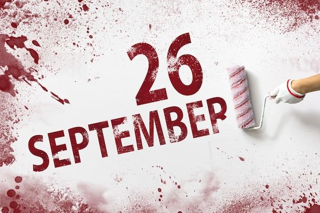 26 de setembro. dia 26 do mês, data do calendário. a mão segura um rolo com tinta vermelha e escreve uma data do calendário em um fundo branco. mês de outono, conceito de dia do ano.