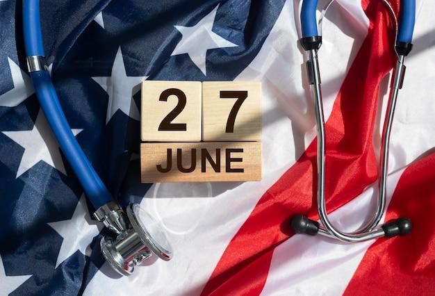 27 de junho no calendário de madeira sobre a bandeira americana.