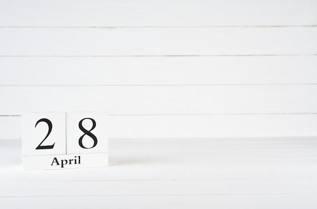 28 de abril, dia 28 do mês, aniversário, aniversário, calendário de bloco de madeira no fundo de madeira branco com espaço da cópia para o texto.
