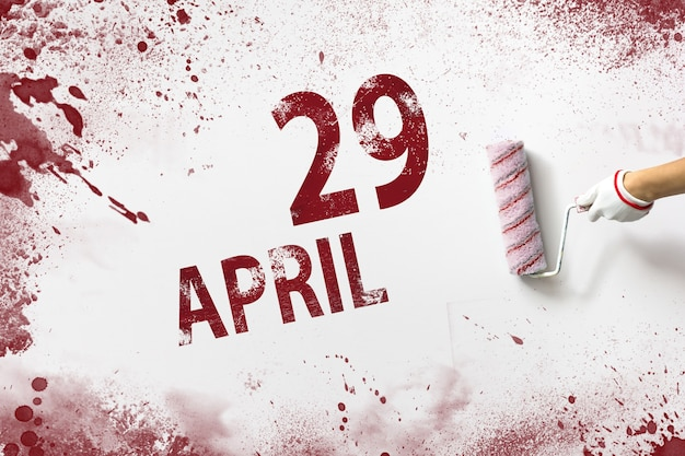 29 de abril. dia 29 do mês, data do calendário. a mão segura um rolo com tinta vermelha e escreve uma data do calendário em um fundo branco. mês de primavera, dia do conceito de ano.