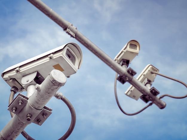 3 câmeras de segurança cctv em um poste alto para proteção pública.