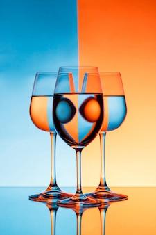 3 copo de vinho com água sobre a parede azul e laranja