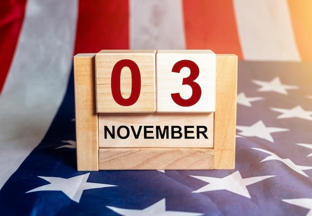 3 de novembro, dia das eleições nos eua. data no calendário de madeira com a bandeira americana no fundo.
