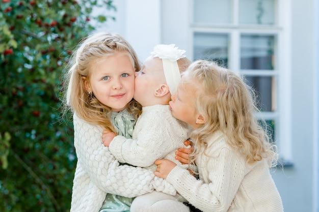 3 meninas com cabelos claros se abraçando. amor pelas irmãs. as meninas do clima amam cada uma delas.