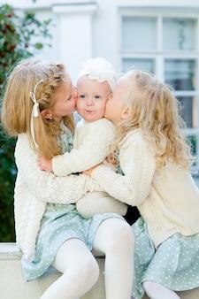 3 meninas com cabelos claros se abraçando. amor pelas irmãs as meninas do clima se amam